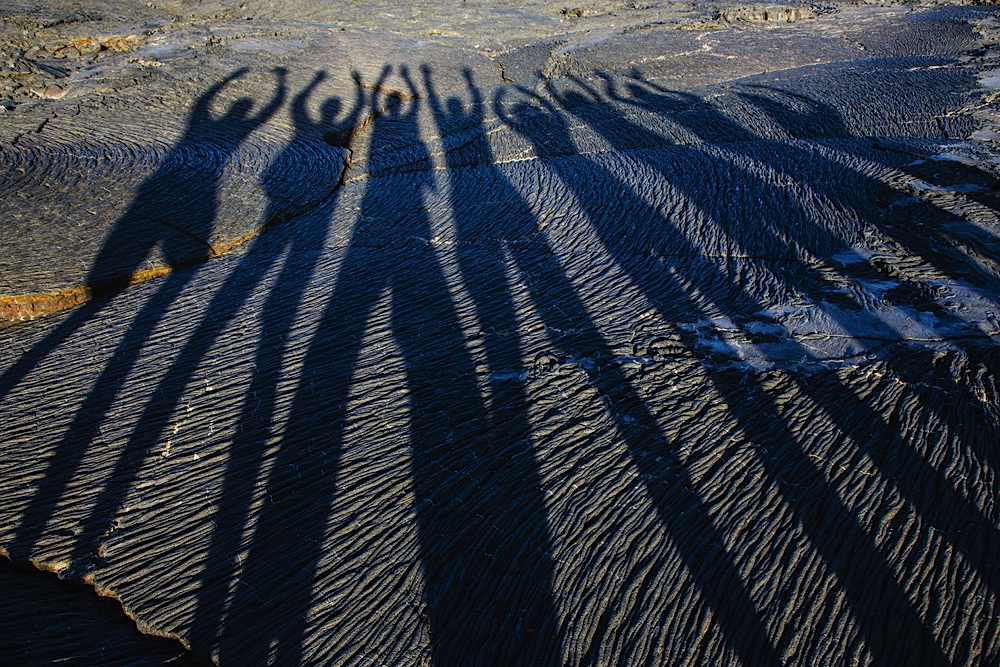 Shadows of a group of people on dry lava flow