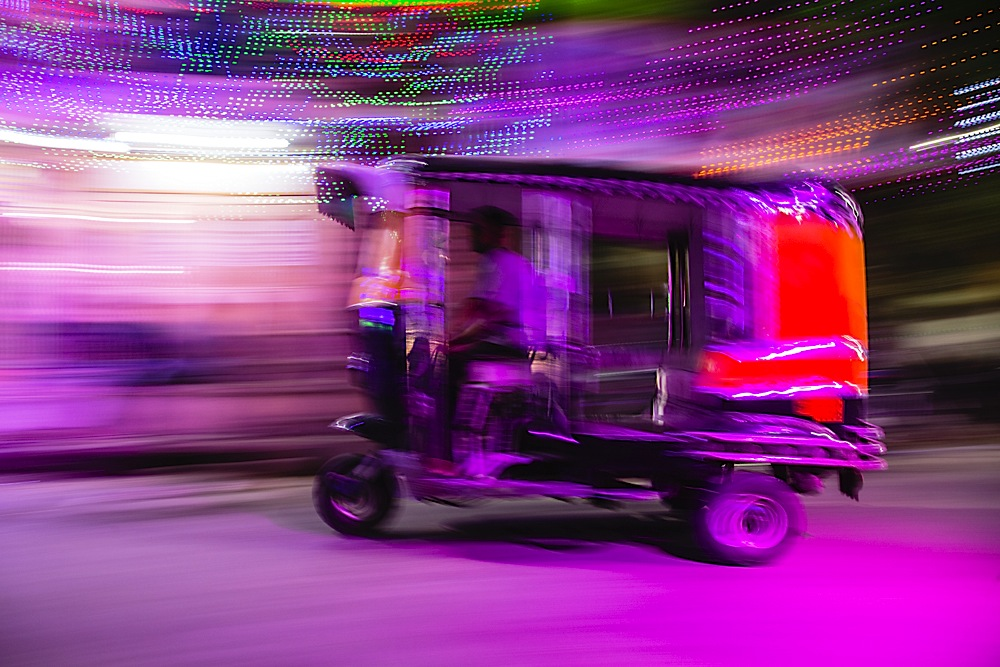 A night time street life scene of a motion-blur of a motorbike taxi in colorful lighting