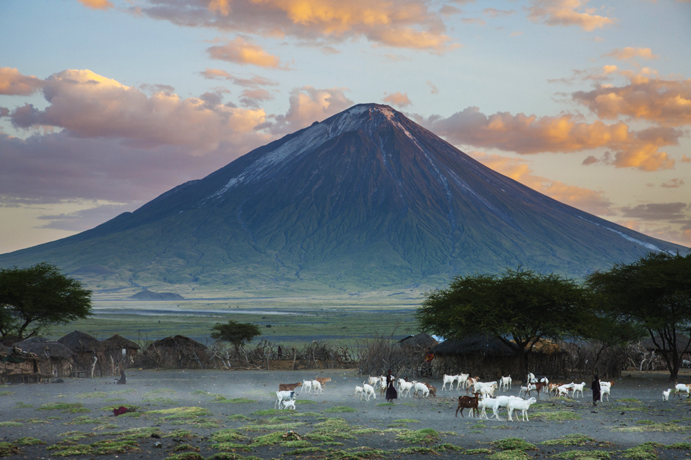 A Masai village at dusk with a volcano behind