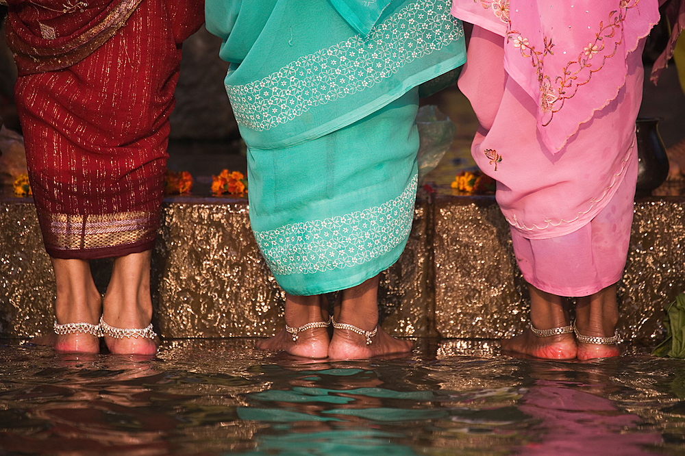 Women in sarees and bracelets around their ankles standing on steps in water of Ganges River