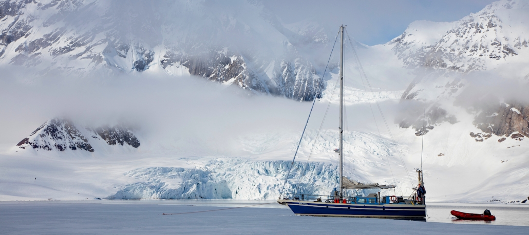 Sail boat Arctic in front of glacier and mountain